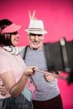 Lycklig hög kvinna som ser maken, medan ta selfie tillsammans fotografering för bildbyråer