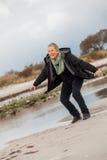 Lycklig hög kvinna som stojar på stranden royaltyfria bilder