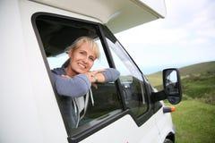 Lycklig hög kvinna som ut ser camparens fönster Royaltyfri Foto