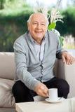 Lycklig hög man som har kaffe på vårdhemmet arkivbild