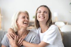 Lycklig hög mogen moder som omfamnar ungt skratta för vuxen kvinna royaltyfri bild