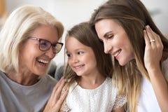 Lycklig hög mormor som omfamnar ungesondotter- och dottermummel arkivbild