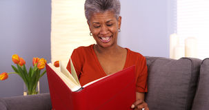 Lycklig hög svart kvinna som ändå ser fotoalbumet arkivfoton