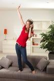 lycklig hörlurar för soffadansflicka Fotografering för Bildbyråer