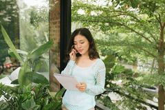 Lycklig h?rlig asiatisk kvinnainnehavbok eller dagbok p? gr?n naturlig utomhus- bakgrund royaltyfri foto