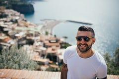 Lycklig handelsresande för ung man som ler på den italienska kustsikten Man som reser till medditerranean europeiskt södra coastE royaltyfri bild
