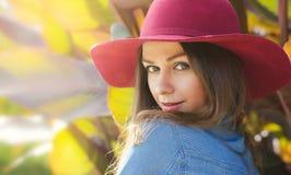 lycklig hattkvinna tät stående Höststående i en utomhus- trädgård Arkivfoto