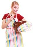 Lycklig hemmafru eller kock i kökförkläde med krukan av sleven Arkivfoto