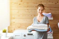 Lycklig hemmafrukvinna i tvättstuga med tvagningmaskinen Royaltyfri Fotografi