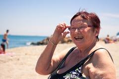 Lycklig hög kvinna på stranden Arkivfoto
