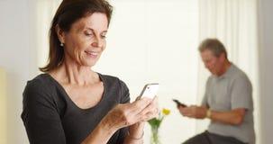 lycklig hög smartphone genom att använda kvinnan Arkivfoto