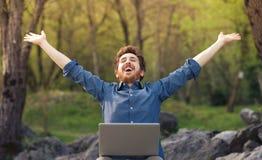 Lycklig hipster med bärbara datorn i skogen arkivbilder