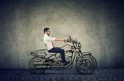 Lycklig hipsteraffärsman som rider en motocycle royaltyfria foton