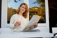 lycklig hipsterflicka som ser i det nästa stället för stadshandbok för att besöka medan frukost i hemtrevlig restaurang Royaltyfri Fotografi