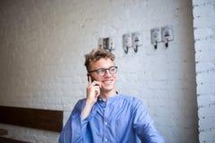 Lycklig hipstergrabb i tillfälliga kläder som har mobiltelefonkonversation under vilotid i kafé arkivbild