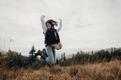 Lycklig hipsterhandelsresande som överst hoppar av berg emotionell mo royaltyfri fotografi