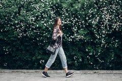Lycklig hipsterkvinna med den svarta påsen som går på bakgrund av blooen Royaltyfri Fotografi
