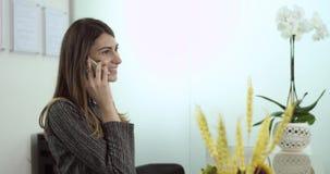 Lycklig hjälp gör en konversation på mottagandeskrivbordet med en klient arkivfilmer