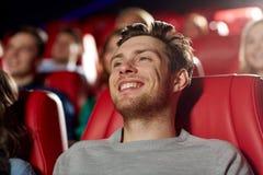 Lycklig hållande ögonen på film för ung man i teater Royaltyfri Bild