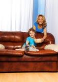 Lycklig hållande ögonen på TV för moder och för pojke att programmera tillsammans Arkivfoton