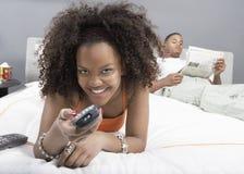 Lycklig hållande ögonen på TV för ung kvinna Arkivfoton