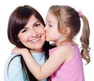 lycklig härlig dotter henne kyssande moder Arkivfoto