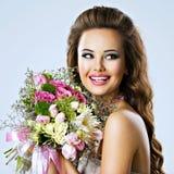 Lycklig härlig flicka med blommor i händer Arkivfoton