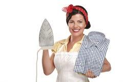 Lycklig härlig kvinnahemmafru som stryker en skjorta Arkivbilder