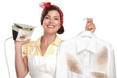 Lycklig härlig kvinnahemmafru som stryker en skjorta Arkivfoton