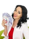 Lycklig härlig ung latinamerikansk kvinna som rymmer en fan av pengar Arkivbild