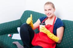 Lycklig hushållerska som dricker kaffe efter fulländande sysslor Fotografering för Bildbyråer