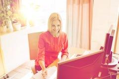 Lycklig idérik kvinnlig kontorsarbetare med datorer arkivbild