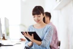 Lycklig idérik kvinnlig kontorsarbetare med minnestavlaPC Arkivfoto
