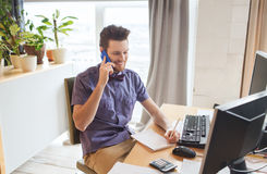 Lycklig idérik manlig arbetare som kallar på smarphone Arkivfoton