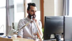 Lycklig idérik manlig kontorsarbetare med datoren lager videofilmer