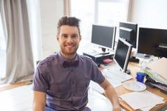 Lycklig idérik manlig kontorsarbetare med datorer arkivfoto