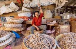 Lycklig indisk affärsman av grönsaker och ingefäran som säljer grönsaker till kunder Arkivfoto