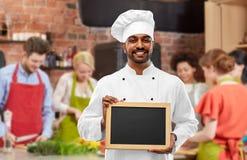 Lycklig indisk kock med den svart tavlan på matlagninggrupp royaltyfri bild