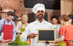 Lycklig indisk kock med den svart tavlan p? matlagninggrupp arkivfoto