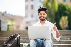 Lycklig indisk student som sitter på trappan som visar tummen upp att arbeta på bärbara datorn, i universitetsområdet Teknologi u royaltyfri bild