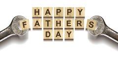 Lycklig inskrift för dag för fader` s på träkuber med funktionsdugliga hjälpmedel på vit bakgrund som isoleras Lyckligt begrepp f royaltyfria foton
