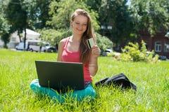 Lycklig internetshoppingkvinna direktanslutet med att sitta för bärbar dator som och för kreditkort är utomhus- Royaltyfri Foto