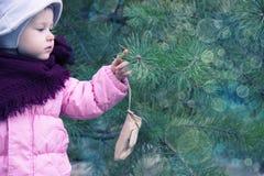 Lycklig jul - Defocused julgranljus för liten flicka och för julgran barnet ser bokehen för ljus för ` s för det nya året royaltyfria foton