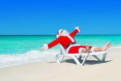 Lycklig jul Santa Claus på vit strandsäng på havstranden Arkivfoton
