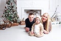 lycklig julfamilj Föräldrarna och behandla som ett barn som ligger på golvet och le Arkivfoton