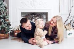 lycklig julfamilj Föräldrarna och behandla som ett barn som ligger på golvet och le Royaltyfri Bild