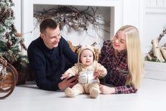 lycklig julfamilj Föräldrarna och behandla som ett barn som ligger på golvet och le Arkivbilder