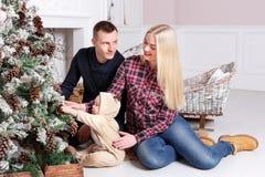 lycklig julfamilj Föräldrarna och behandla som ett barnsammanträdet på golvet och le Arkivfoton