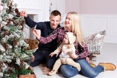 lycklig julfamilj Föräldrarna och behandla som ett barnsammanträdet på golvet och le Royaltyfri Bild