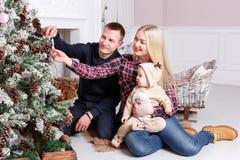 lycklig julfamilj Föräldrarna och behandla som ett barnsammanträdet på golvet och le Royaltyfri Fotografi